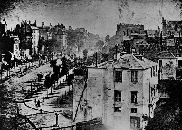 """Oto na fotografii Boulevard du Temple pojawił się człowiek. Jest to pierwsza fotografia, na której utrwalono postać człowieka, oczywiście utrwalili się przechodnie, którzy przytanęli dłuższą chwilę, pozostali """"rozmyli się"""". Louis Jacques Mandé Daguerre 1838"""
